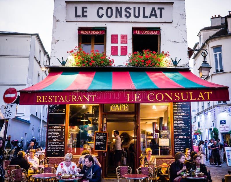 Le Consulat Restaurang, Montmartre, yttersida med matställear som placeras på kafétabeller arkivbild