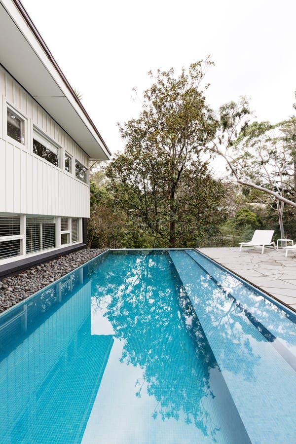 Le contemporain a entièrement couvert de tuiles la piscine dans le hom moderne de la moitié du siècle image libre de droits