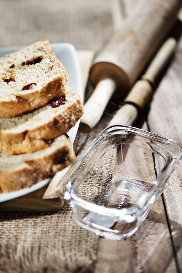 Le conteneur en verre vide sur un conseil en bois, accompagné des tranches de pain de blé de raisin sec ou de raisins secs a serv images libres de droits