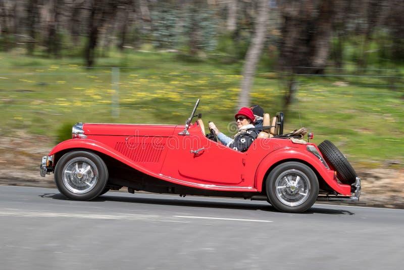 Le convertible rouge de vintage folâtre la conduite sur la route de campagne image stock