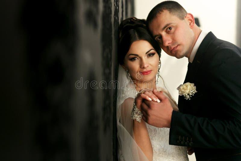 Le coppie adorabili nell'amore stanno la parete vicina fotografia stock libera da diritti