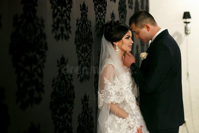 Le coppie adorabili nell'amore stanno la parete vicina fotografie stock libere da diritti