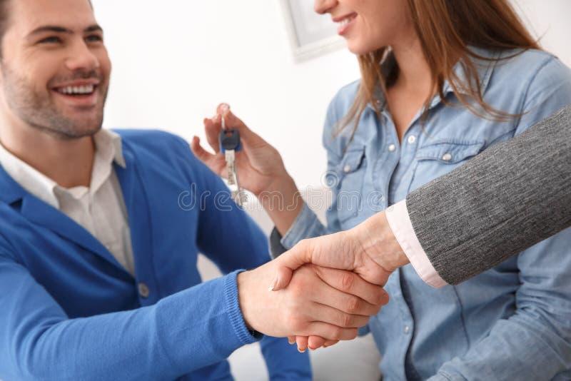 Le coppie all'ufficio vendite del bene immobile con l'agente che stringe le mani trattano immagini stock