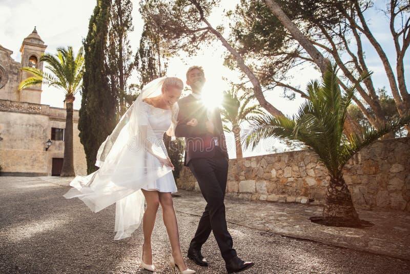 Le coppie alla moda di nozze si avvicinano alla chiesa cattolica Sposa e sposo Ritratto esterno fotografie stock