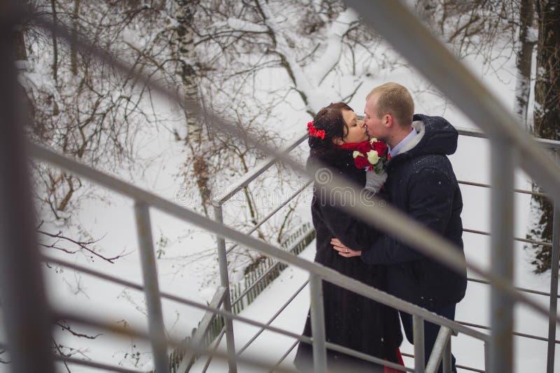 Le coppie amorose, lo sposo e la sposa, bacio sulla via nell'inverno fotografia stock