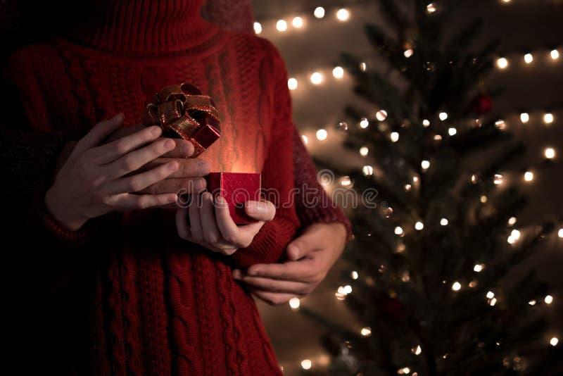 Le coppie aprono il contenitore di regalo di Natale con le luci brillanti sul fondo del bokeh fotografia stock libera da diritti