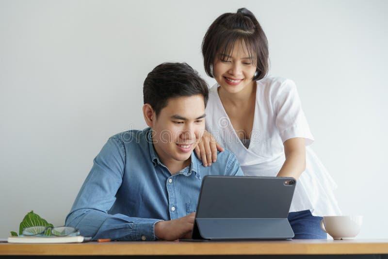 Le coppie asiatiche di amore si siedono la sedia nel salone e lavorare alla compressa che stanno sorridendo felicemente immagine stock libera da diritti