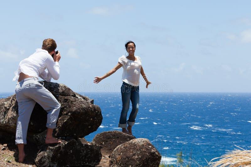 Le coppie attraenti catturano la foto sulla scogliera in Hawai fotografie stock