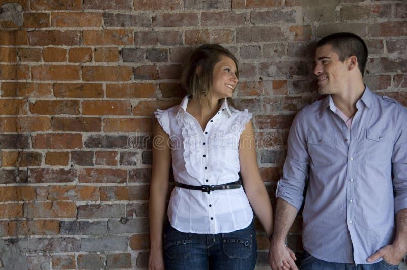 Le coppie attraenti tengono le mani fotografia stock
