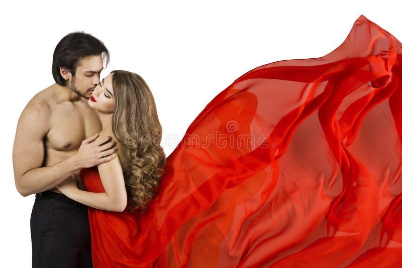 Le coppie baciano, uomo sexy che bacia la bella donna, ragazza in vestito d'ondeggiamento rosso fotografia stock