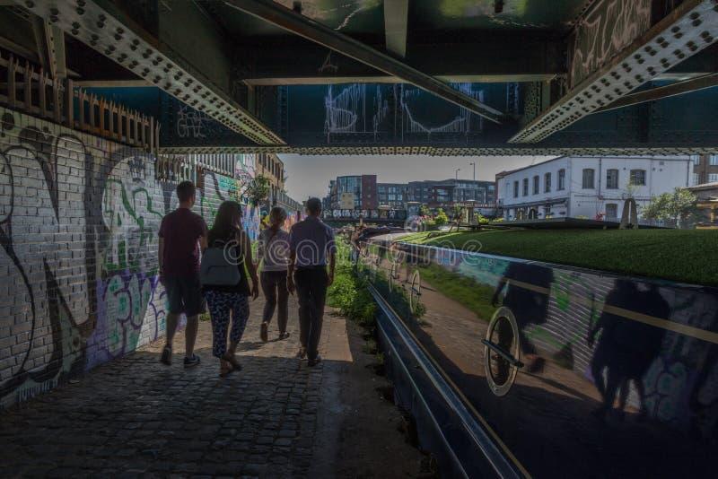 Le coppie camminano sotto un ponte sul fiume Lea London immagine stock