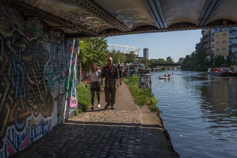 Le coppie camminano sotto un ponte sul fiume Lea London fotografia stock libera da diritti