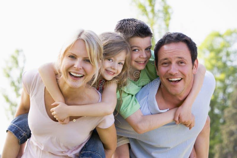 Le coppie che danno due bambini trasportano sulle spalle sorridere di giri