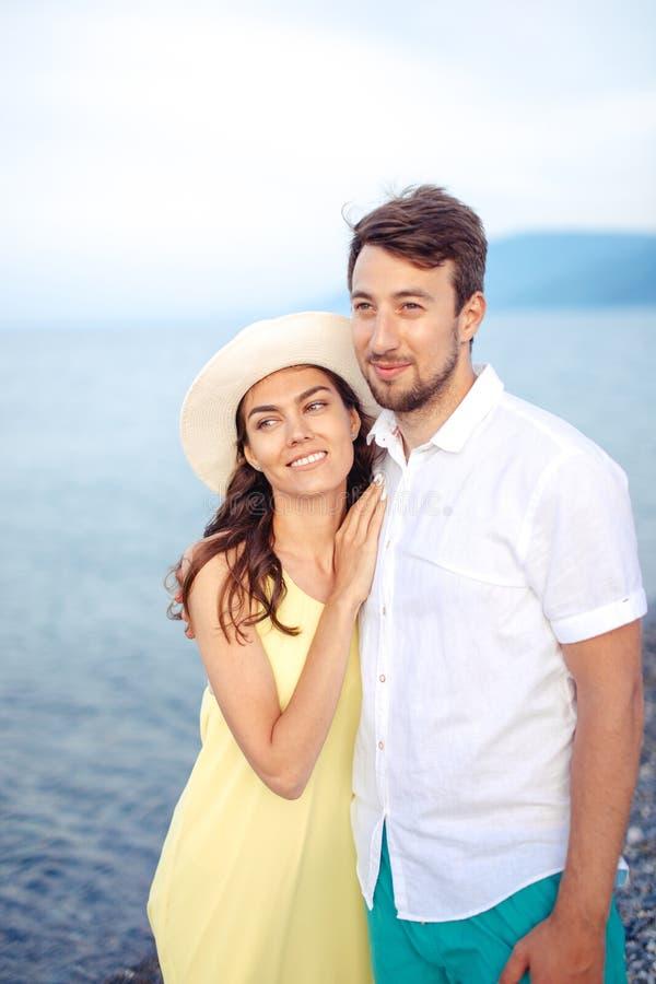 Le coppie che si tengono per mano sulla spiaggia e sulla passeggiata e godono di insieme immagini stock libere da diritti