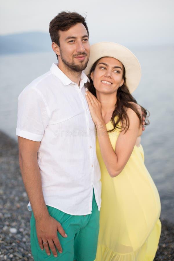 Le coppie che si tengono per mano sulla spiaggia e sulla passeggiata e godono di insieme fotografie stock