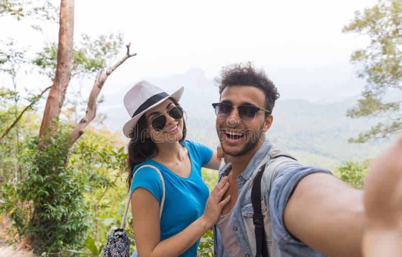 Le coppie con gli zainhi prendono la foto di Selfie sopra trekking del paesaggio della montagna, il giovane e la donna sui turist fotografie stock libere da diritti