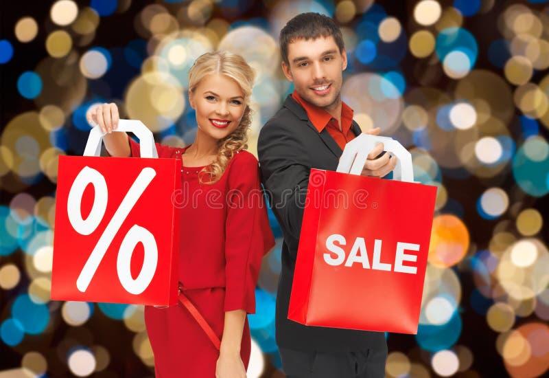 Le coppie con la vendita e lo sconto firmano sul sacchetto della spesa fotografia stock libera da diritti