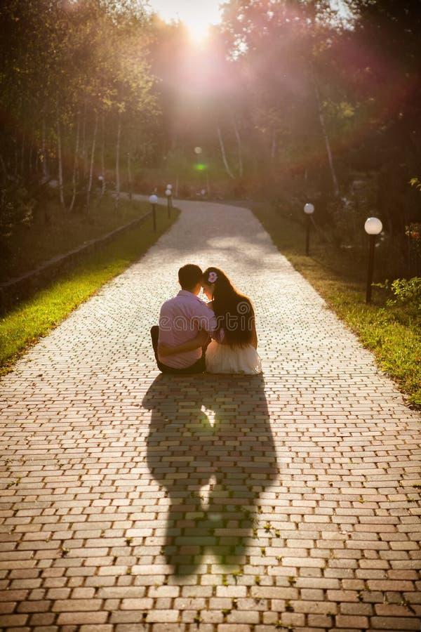 Le coppie degli adolescenti si siedono insieme in via immagine stock