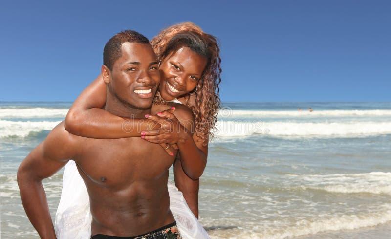 Le coppie dell'afroamericano che sorridono sulla spiaggia Outdo immagini stock