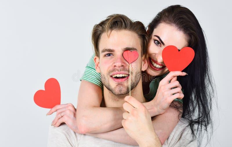 Le coppie della donna e dell'uomo nell'abbraccio di amore e tenere le carte rosse dei biglietti di S. Valentino del cuore si chiu fotografia stock