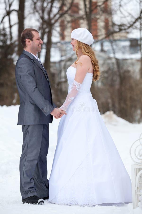 Le coppie della persona appena sposata che stanno nell'inverno parcheggiano in vestito ed il vestito, si tiene per mano e guardan immagine stock