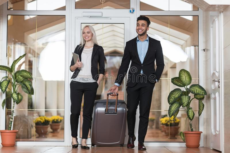 Le coppie di affari nell'ingresso dell'hotel, nell'uomo del gruppo delle persone di affari e negli ospiti della donna arrivano immagini stock