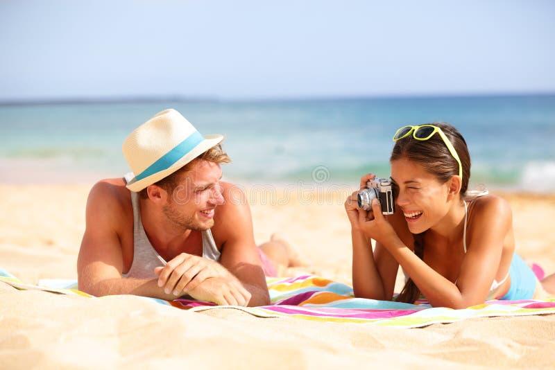 Le coppie di divertimento della spiaggia viaggiano - donna che prende la foto fotografia stock