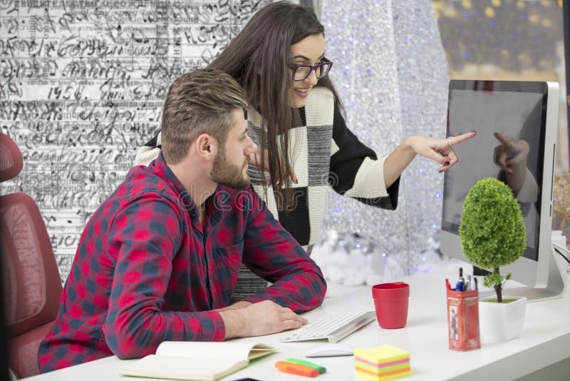 Le coppie di giovani progettisti che lavorano all'ufficio moderno, due colleghe che discutono il divertimento proiettano sopra un fotografie stock libere da diritti