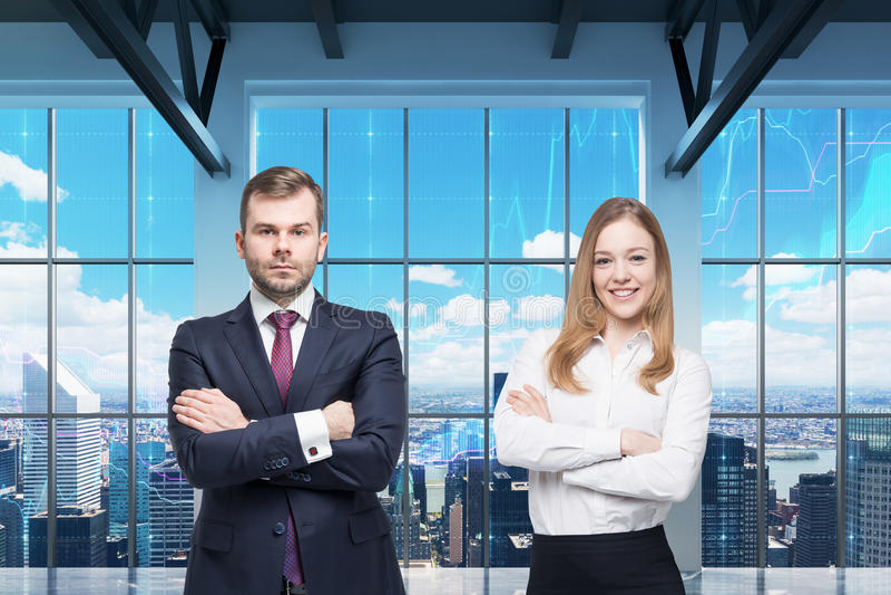 Le coppie di giovani responsabili stanno stando nell'ufficio panoramico moderno Vista di New York I grafici finanziari sono tracc fotografia stock libera da diritti