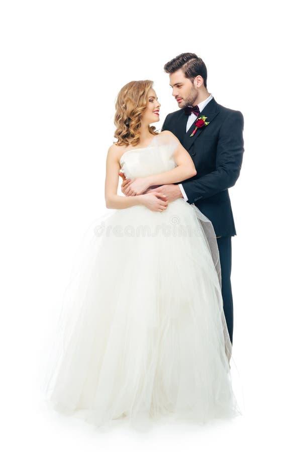 Le coppie di nozze che se esaminano hanno isolato su bianco immagine stock libera da diritti