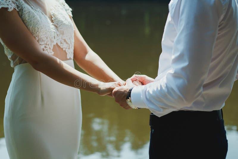 Le coppie di nozze stanno sul pilastro di legno e tengono le mani Esaminano la bella vista sopra il lago Giorno di estate soleggi immagini stock