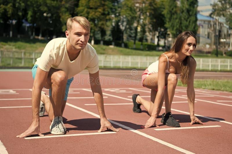 Le coppie di sport iniziano il funzionamento della concorrenza alla pista dell'arena fotografia stock