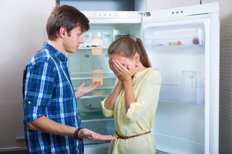 Le coppie difficili si avvicinano al frigorifero vuoto fotografia stock