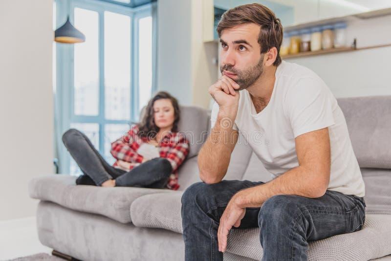 Le coppie discutono La moglie ha gridato al suo marito disperato, sedentesi sullo strato nel salone a casa Un uomo non fa immagine stock