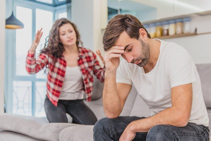 Le coppie discutono La moglie ha gridato al suo marito disperato, sedentesi sullo strato nel salone a casa Un uomo non fa immagini stock libere da diritti
