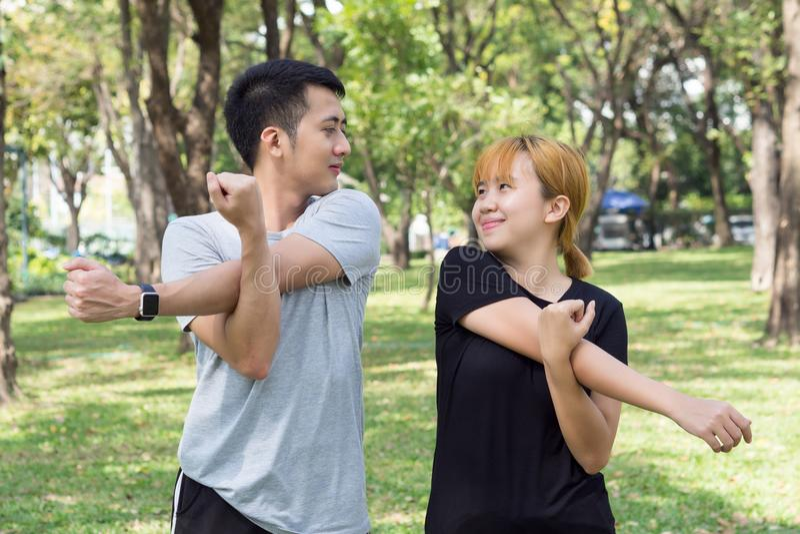 Le coppie dolci asiatiche si scaldano i loro corpi allungando le armi prima dell'esercizio pareggiante di mattina nel parco fotografie stock libere da diritti