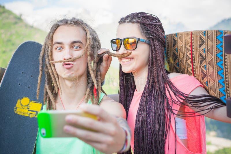 Le coppie fanno il selfie sul telefono cellulare, facente i baffi dei capelli fotografia stock