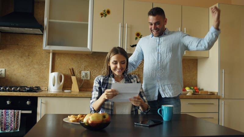 Le coppie felici attraenti ricevono la lettera di spiegamento di buone notizie nella cucina mentre abbia prima colazione a casa fotografia stock