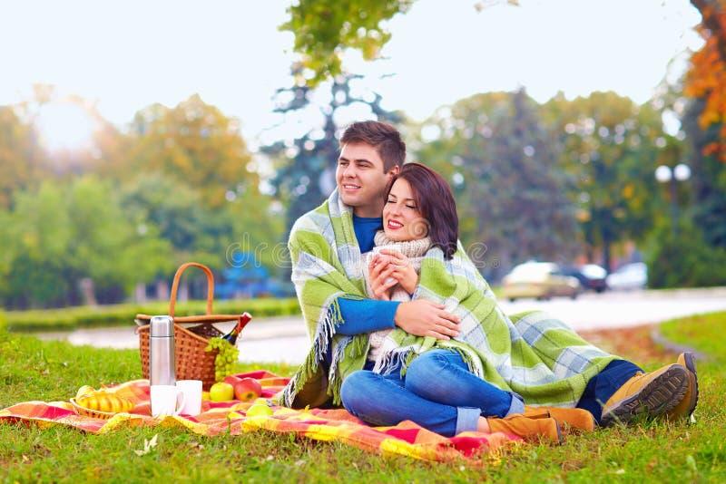 Le coppie felici che godono dell'autunno fanno un picnic nel parco della città fotografia stock