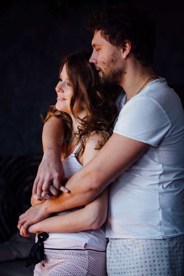 Le coppie felici degli amanti in pigiami equipaggiano l'abbraccio della ragazza da dietro immagini stock libere da diritti