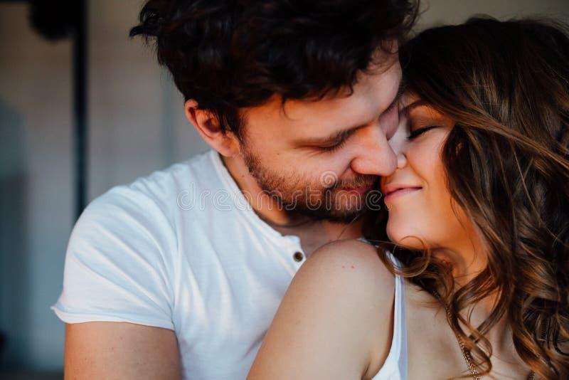 Le coppie felici degli amanti in pigiami equipaggiano l'abbraccio della ragazza da dietro Occhi chiusi immagine stock libera da diritti