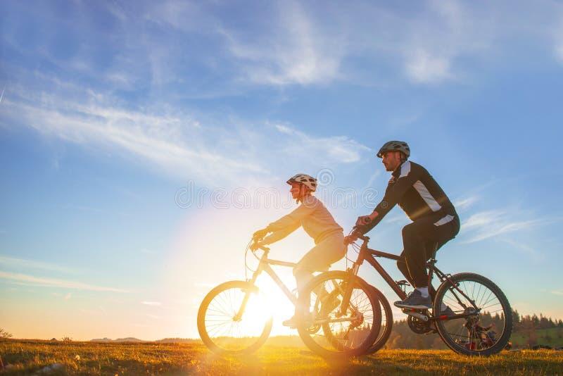 Le coppie felici del mountainbike all'aperto si divertono insieme su un tramonto di pomeriggio dell'estate immagini stock