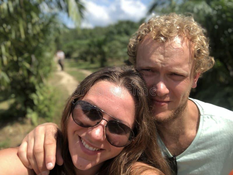 Le coppie felici del tipo dalla carnagione chiara e della ragazza sul mare nei tropici godono insieme della vita, felice Selfie fotografia stock