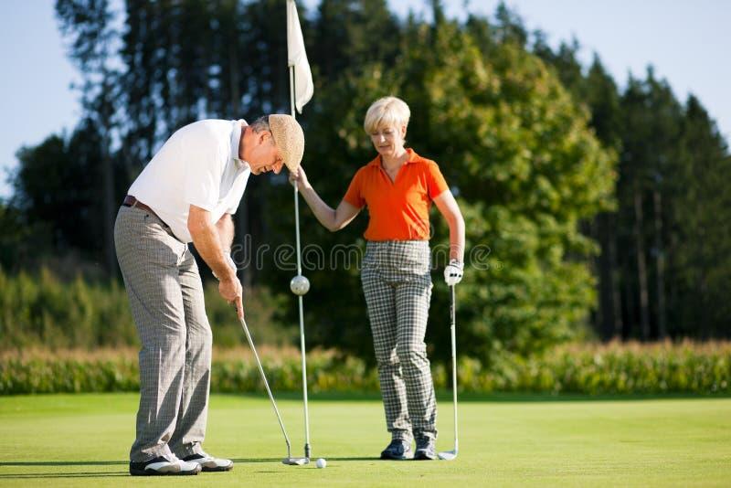 le coppie golf il gioco maturo fotografia stock libera da diritti