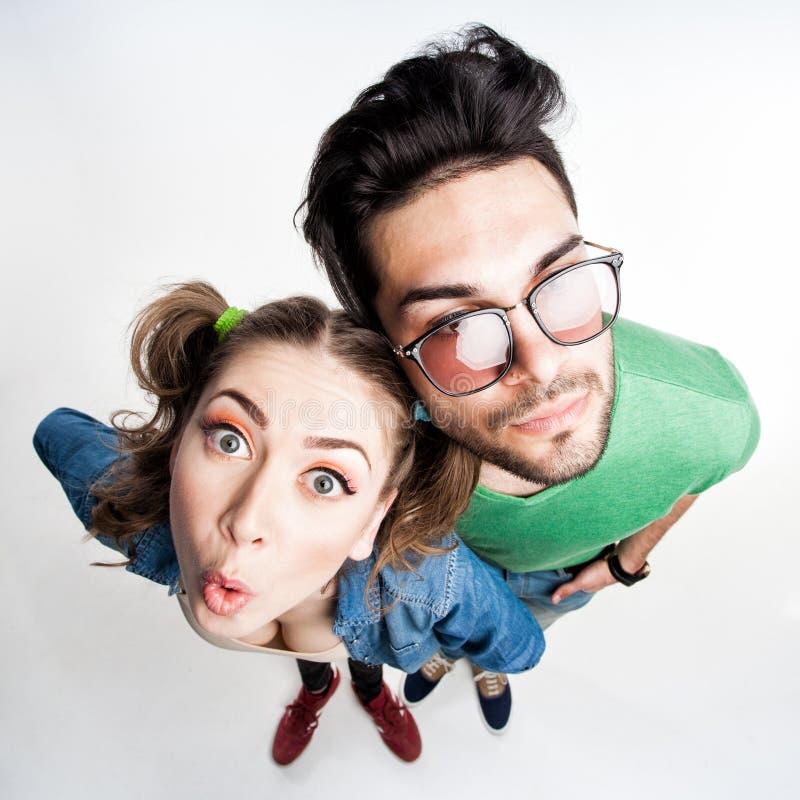 Le coppie graziose hanno vestito i fronti divertenti di fabbricazione casuali - colpo grandangolare fotografia stock