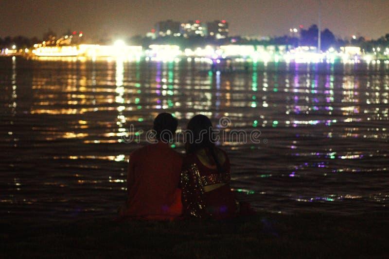 Le coppie hanno macchiato la seduta insieme e godere delle luci immagini stock
