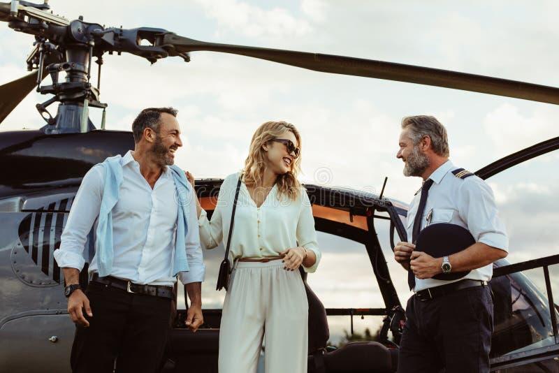 Le coppie hanno sceso da un elicottero che ringrazia il pilota immagini stock