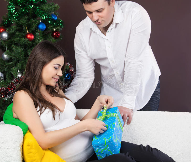 Le coppie incinte felici si avvicinano all albero di Natale