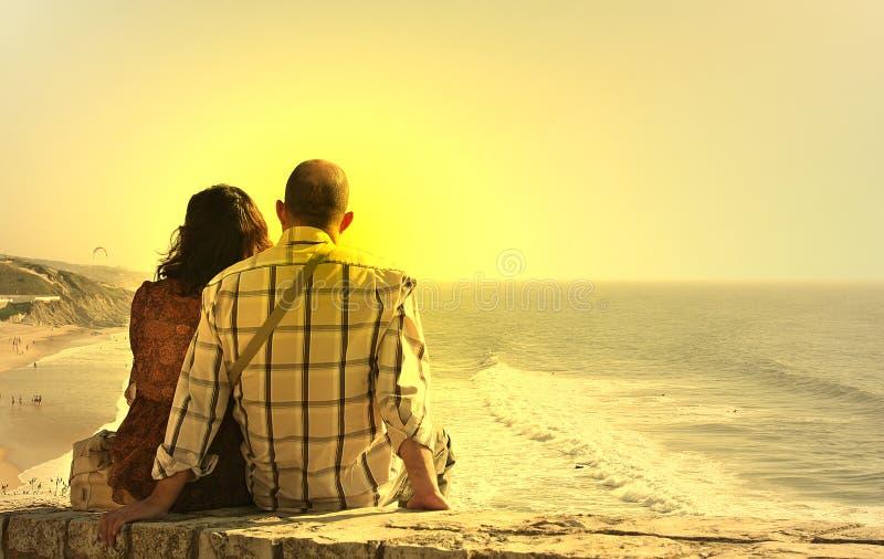 Le coppie messe guardano il tramonto fotografia stock
