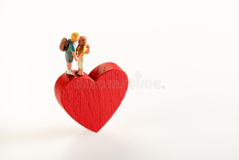 Le coppie miniatura nella tenuta di amore su un cuore modellano immagine stock libera da diritti